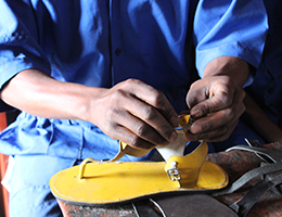 A photo of Christian Bayisenge shoemaking